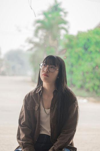 Thoughtful beautiful young woman sitting outdoors