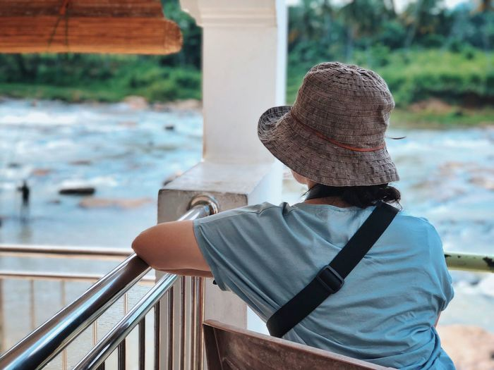 Rear view of woman looking at sea while sitting by railing