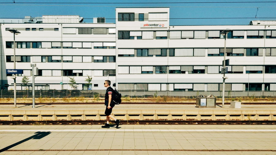 Side view of man on railroad tracks by buildings in city