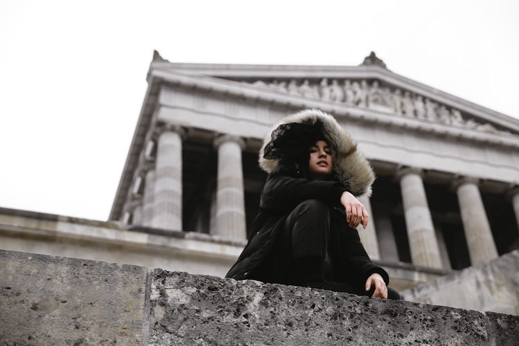 Low angle view of woman sitting against building
