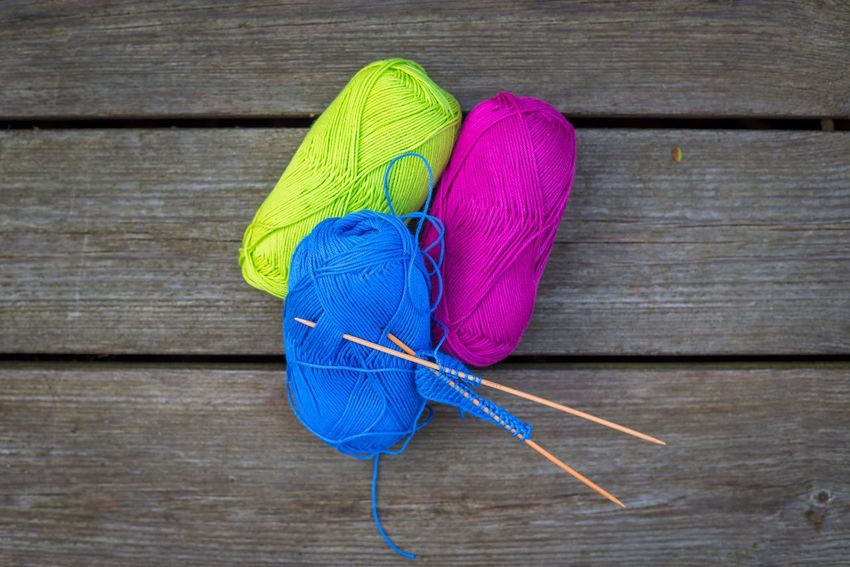 Knit wear on the wooden table in various colors Knit Wood - Material Art And Craft Wool Craft Still Life No People Table Indoors  Creativity High Angle View Knitting Needle Ball Of Wool Directly Above Material Blue Purple Close-up Multi Colored Textile Pink Color