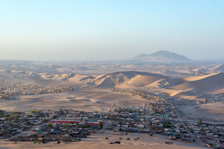 Village In Desert Against Clear Sky At Huacachina