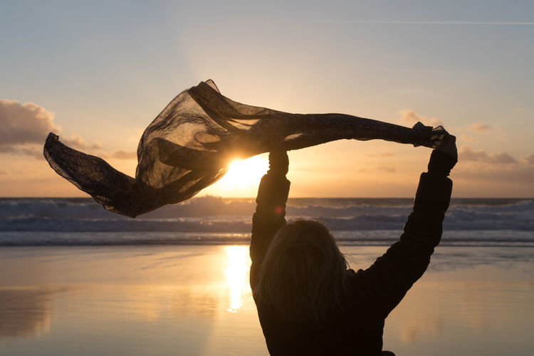 Rear view of woman holding scarf while standing at beach against sky