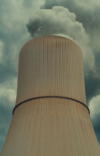 Low angle view of smoke emitting from chimney against cloudy sky