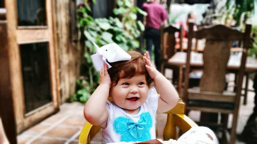 Happy playful girl sitting in chair at sidewalk cafe
