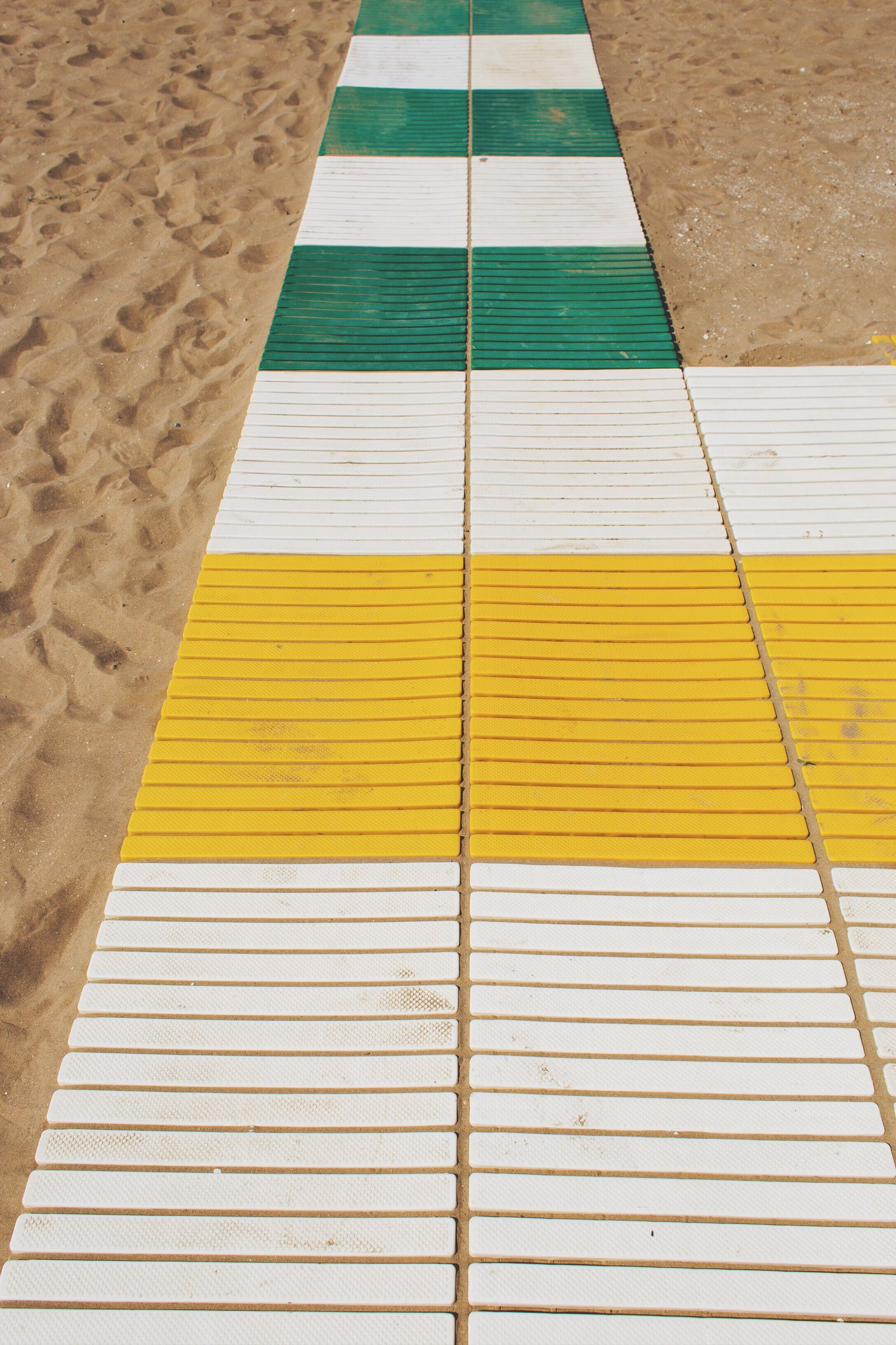 yellow, high angle view, no people, pattern, architecture, day, multi colored, outdoors, full frame, built structure, absence, flooring, backgrounds, striped, footpath, wall - building feature, close-up, line, tile, single line, tiled floor, swimming pool, dividing line
