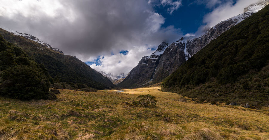 A dramatic shot of a valley on the Routeburn track. Cloudy Hiking Sunlight Travel Trekking Beauty In Nature Grass Idyllic Landscape Meadow Mountain Mountain Range Mountains Nature New Zealand No People Outdoors Routeburn Track Scenics Tranquility Valley