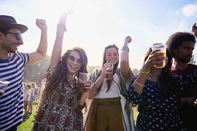 Friends holding beer in glasses while standing on grass