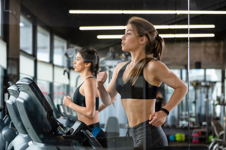Beautiful young women running on treadmills in gym