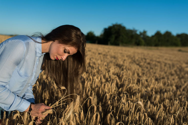 Beautiful young woman looking at wheat on field against sky