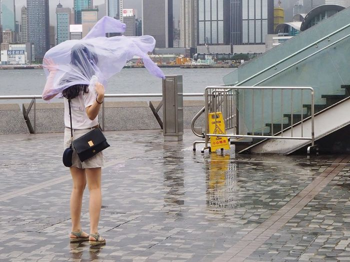 Full length of woman wearing raincoat while standing in city