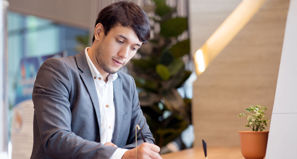 View of business person writing in office