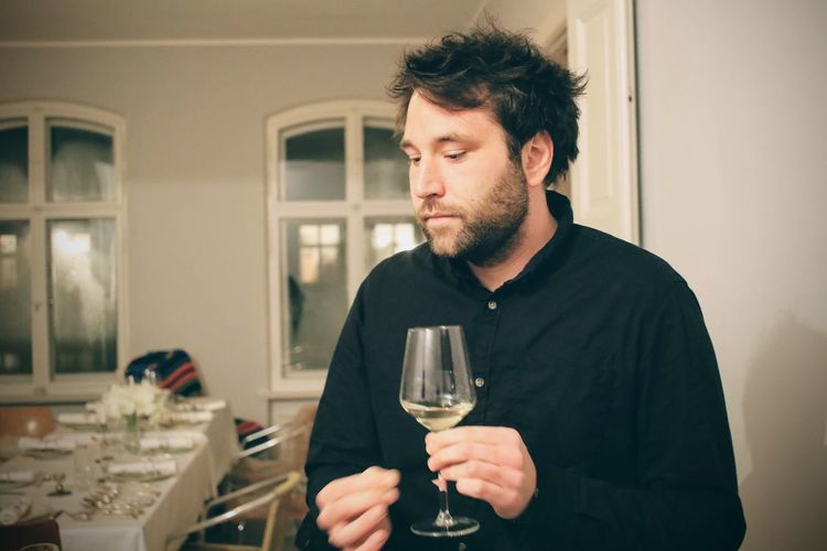 Thoughtful man looking down while holding wineglass