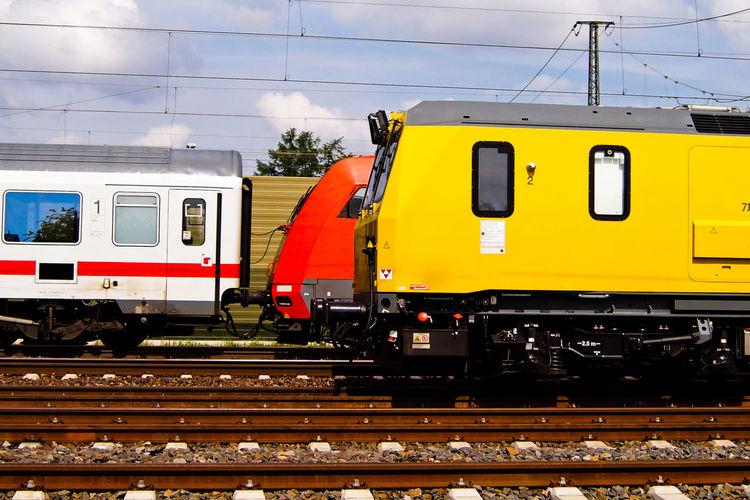 Passenger Trains On Tracks Against Sky