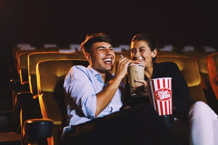Happy couple having drink while sitting in movie theater