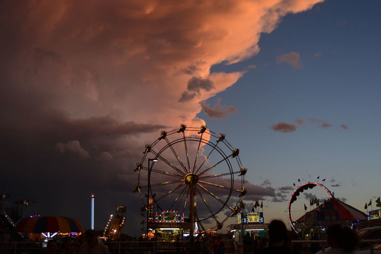 Ferris wheel in city against sky at sunset