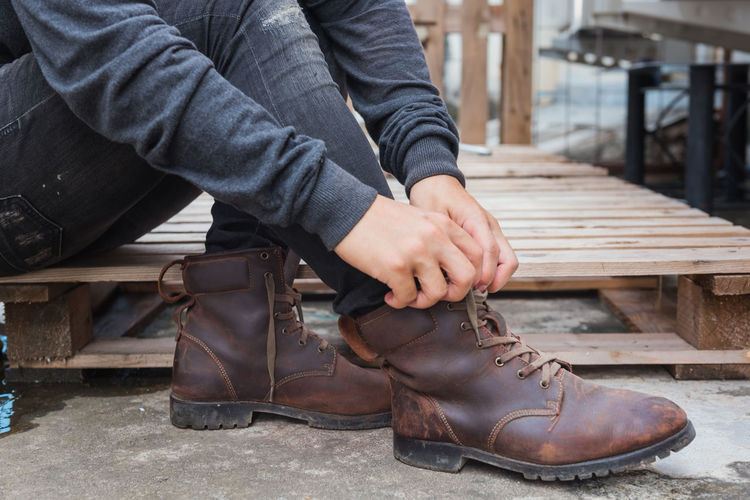 Bench Brown Casual Clothing Day Finger Focus On Foreground Hand Human Body Part Human Hand Leather Leisure Activity Lifestyles Low Section Men One Person Outdoors Real People Seat Shoe Sitting Wood - Material