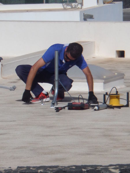 Electrician  Full Length Male Male Figure Person Person Crouching Rooftop Single Person Sunshine Tools Working Working Day. Workman On A Roof.