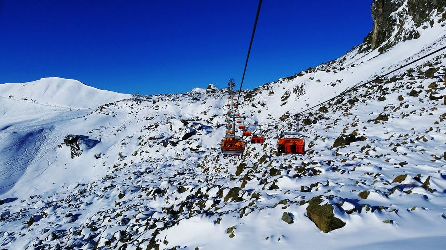 Ski Lifts On Snow Covered Mountains Against Sky