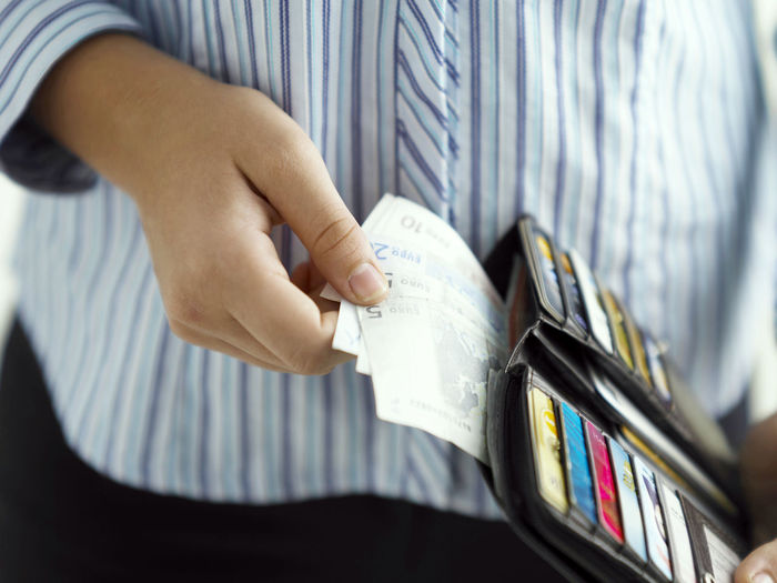 Midsection Of Woman Holding Paper Currency In Purse