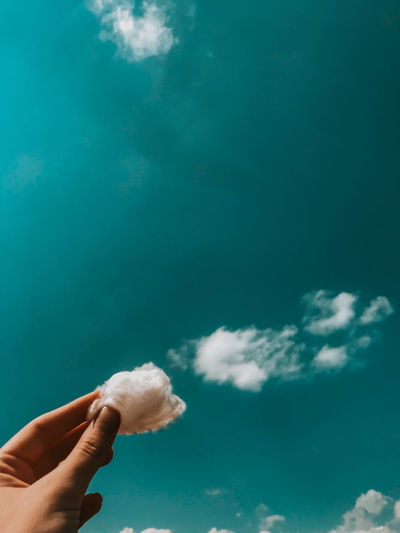 Person holding cotton against sky