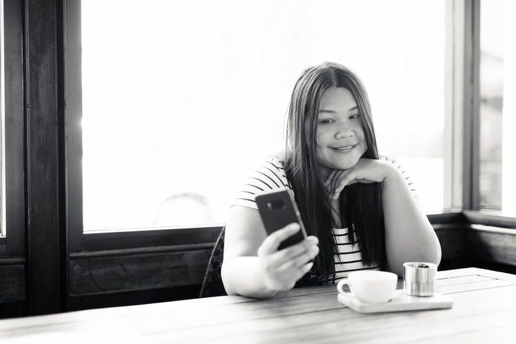 Portrait of woman using phone at coffee shop