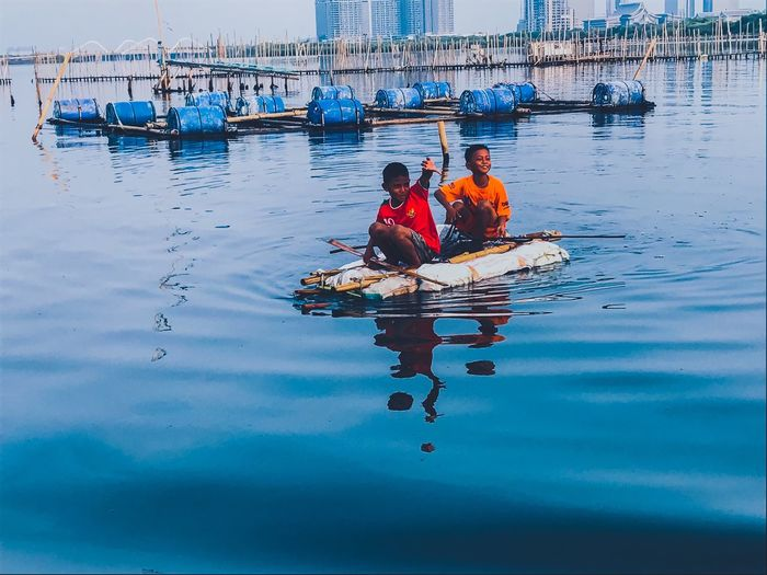 Reflection of people on boat in sea