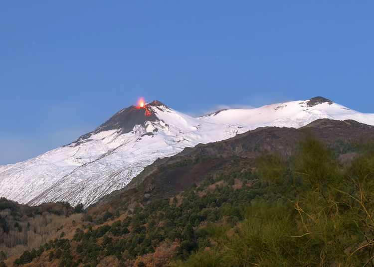 Low angle view of snowcapped volcano erupting against blue sky