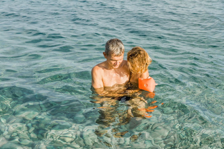 Rear view of father and daughter in sea