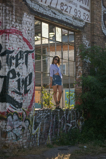 Young Woman Standing On Window Sill Amidst Graffiti Wall