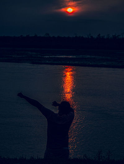 Rear view of man standing by river during sunset