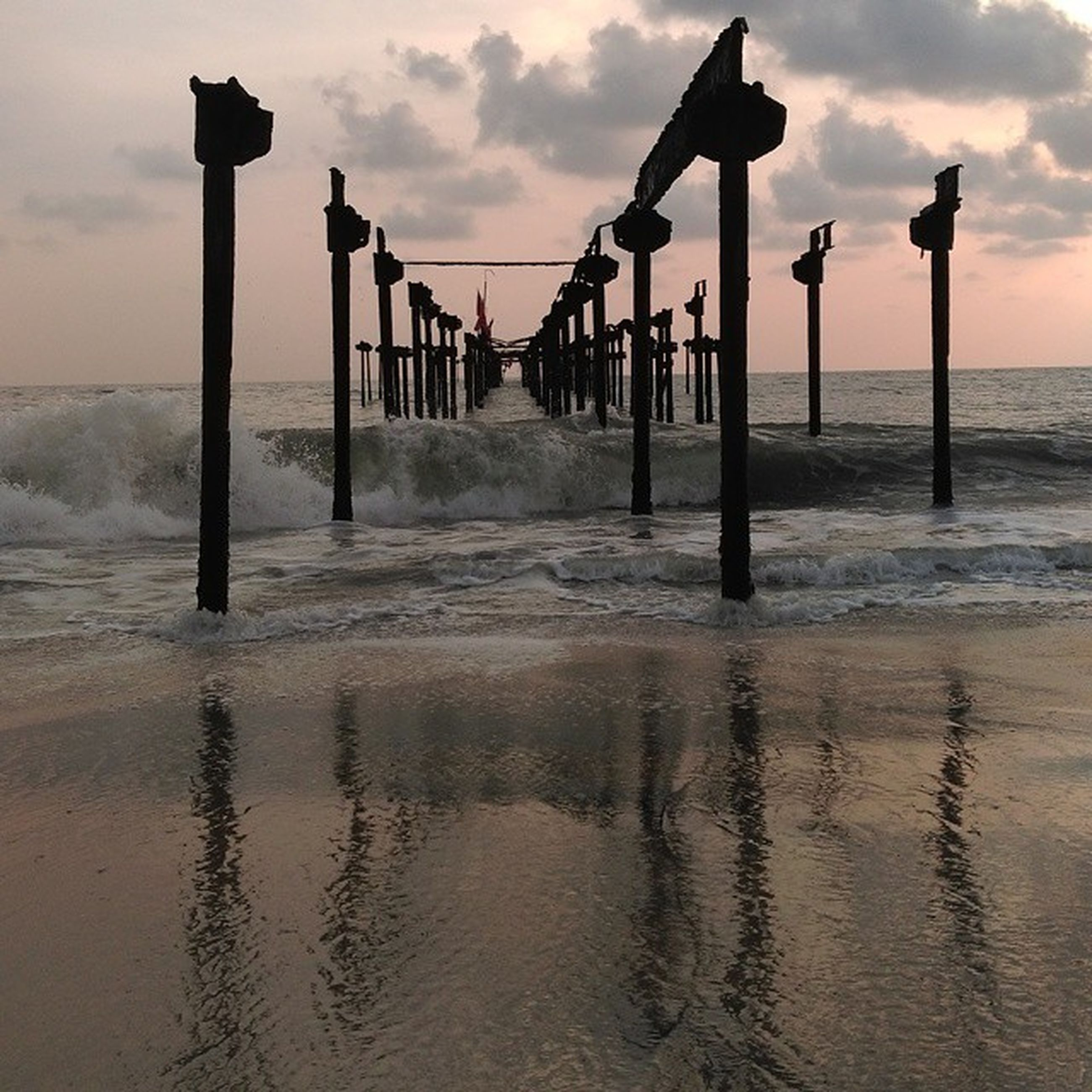 sea, water, sky, beach, sunset, pier, built structure, in a row, cloud - sky, architecture, tranquility, horizon over water, wooden post, shore, scenics, tranquil scene, beauty in nature, nature, architectural column, sand