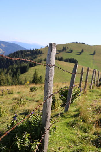 Wooden fence on field against sky