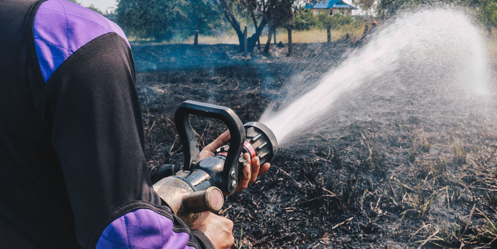 Midsection of man spraying water on land