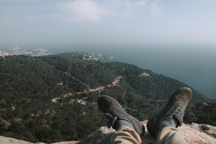 Low section of person relaxing on mountain by sea against sky