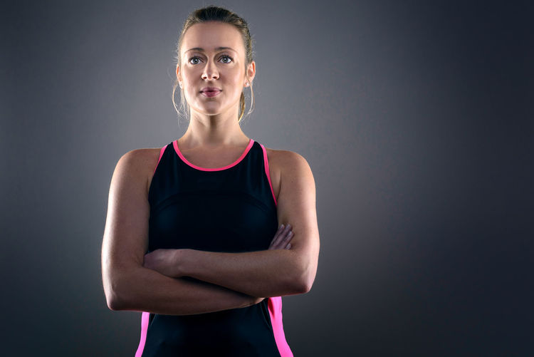Portrait of athlete standing with arms crossed against gray background