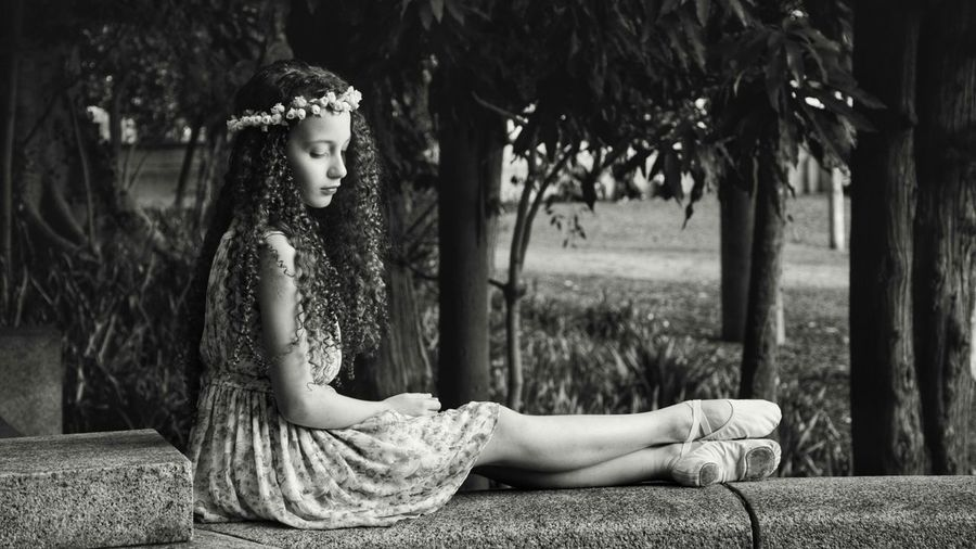 Side view of girl with curly hair sitting on retaining wall in park
