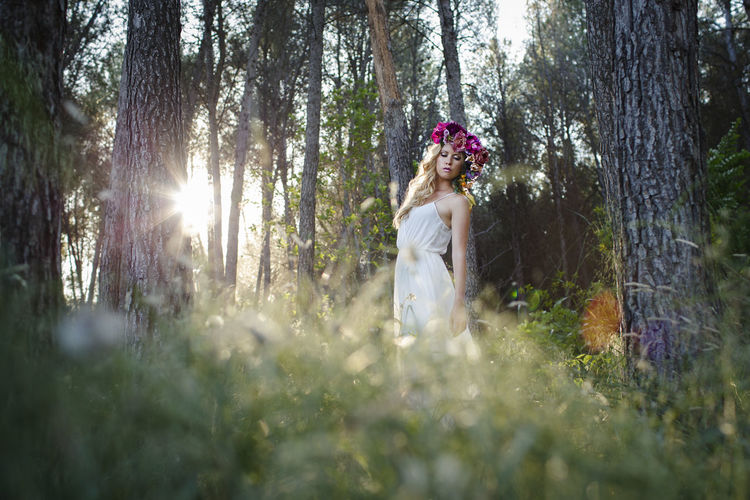 Blond Caucasian woman with wavy hair, posing in romantic style in the forest. Young beautiful bride wearing elegant white dress, flowers and backlight Activity Adult Couple - Relationship Day Forest Growth Land Leisure Activity Lens Flare Lifestyles Nature Outdoors People Plant Real People Selective Focus Sunlight Tree Tree Trunk Trunk Women WoodLand Young Adult