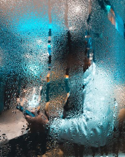 Side view of person using phone seen through wet window