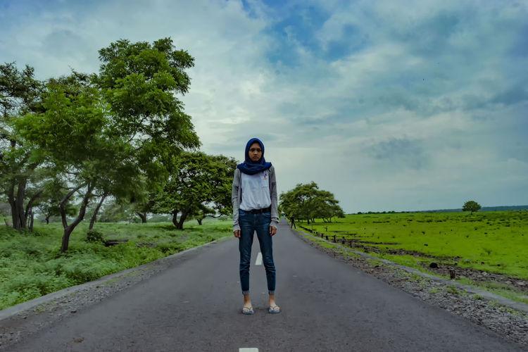 Full length of girl standing on field against sky