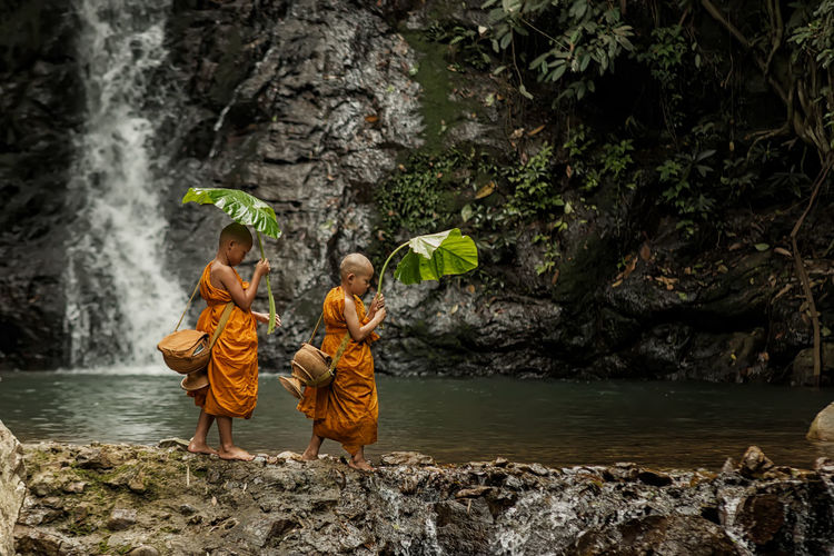 Monks with plants walking at waterfall