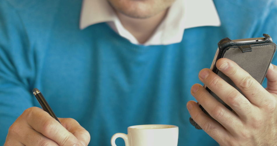 Close-up of man holding coffee cup