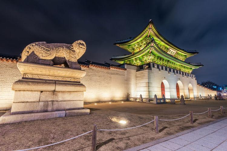 Animal Sculpture By Illuminated Gate At Night