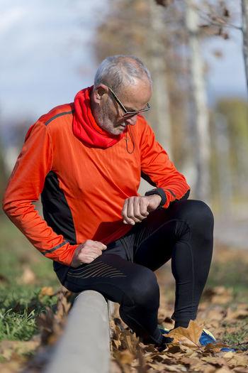 Senior Man Checking Time While Sitting At Park