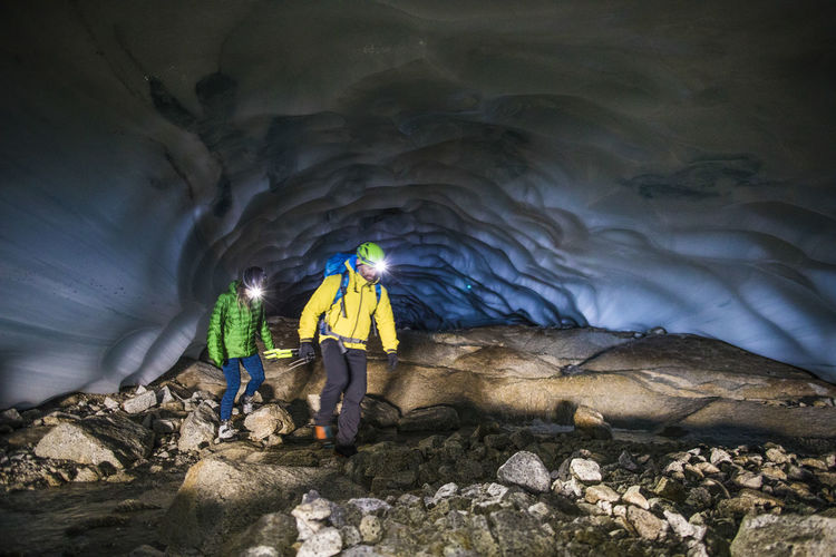Rear view of people walking in cave