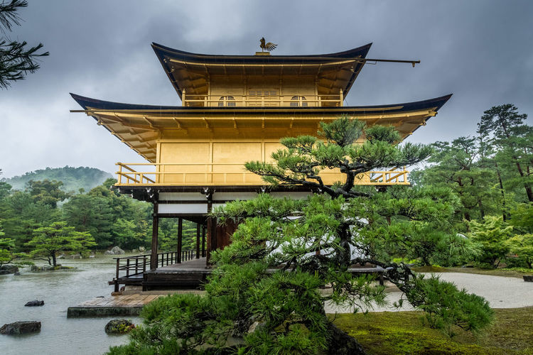 "Kinkaku-ji (金閣寺, literally ""Temple of the Golden Pavilion""), officially named Rokuon-ji (鹿苑寺), is a Zen Buddhist temple in Kyoto, Japan. It is one of the most popular shrine in Japan, Photos were taken on a rainy (monsoon) day... Plant Tree Nature Built Structure Architecture Sky Building Exterior Religion Belief No People Water Place Of Worship Spirituality Outdoors Dramatic Sky Kyoto Shrine Temple Pond Lake Rainy Day Golden Gold Leaf Kinkakuji EyeEm Selects"