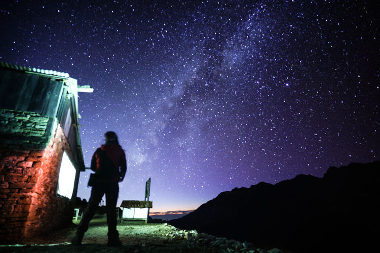 Low Angle View Of Woman Standing Against Star Field At Night