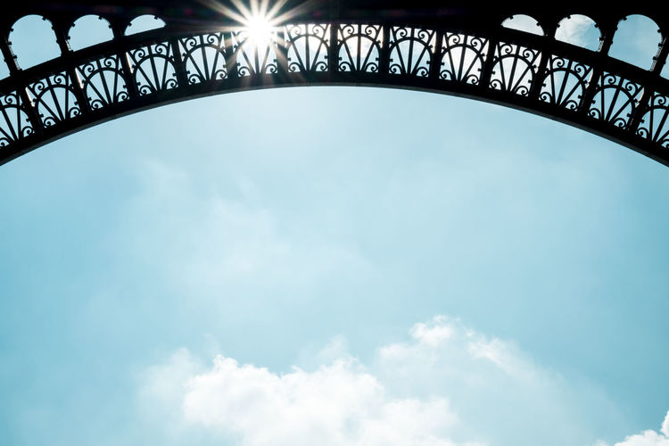 Arch Architecture Art Art Culture And Entertainment Blue Built Structure City Cloud - Sky Copy Space Day Eiffel Tower Famous Place Lens Flare Low Angle View No People Outdoors Pattern Sky Steel Sunlight Tourism Tower Travel Travel Destinations Vacations