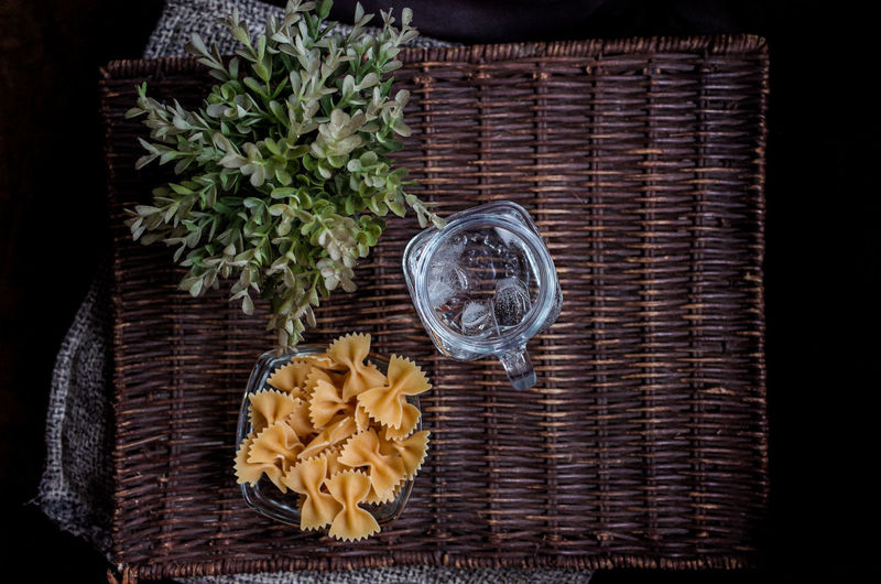 Directly Above Shot Of Farfalle Pasta And Drinking Water On Wicker Mat