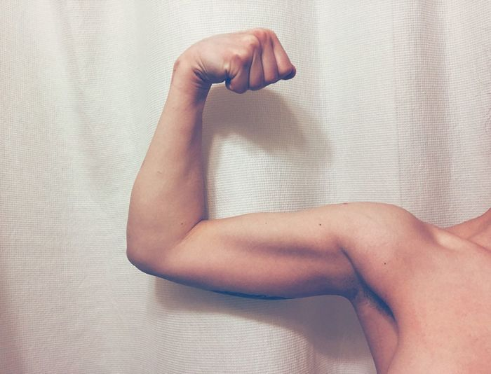 Cropped Image Of Teenage Boy Flexing Biceps While Standing Against Curtain
